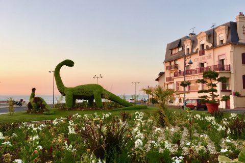Façade Hôtel Outre-Mer (Villa Le couchant) et dinosaure au soleil couchant en été
