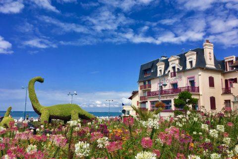 Façade de l'Hôtel Outre-Mer en été et vue sur le dinosaure de Villers sur Mer